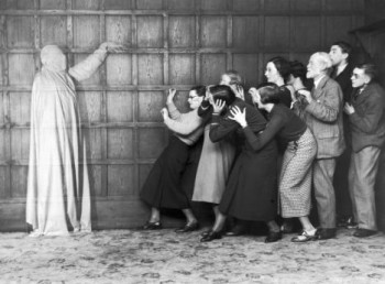 People cowering in fear at the sight of a ghost, c 1920s.