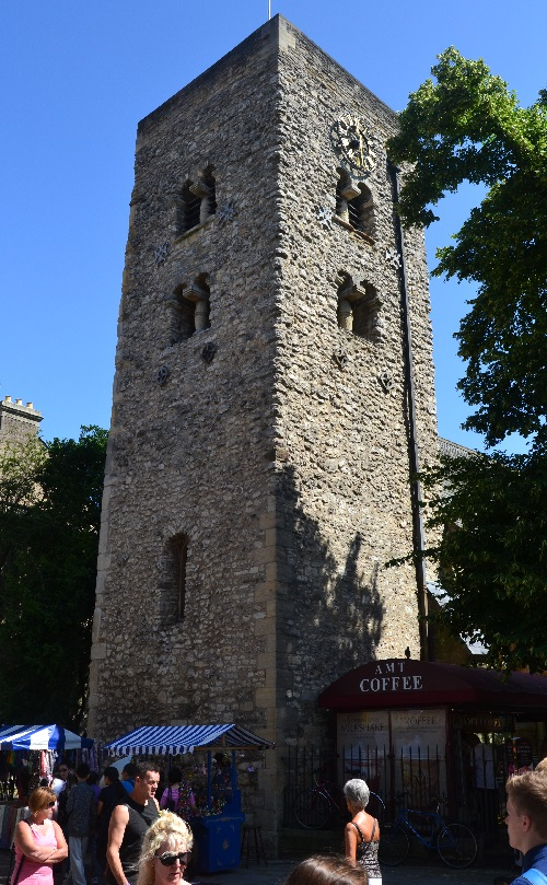 The Saxon Tower rises above a busy shopping street.