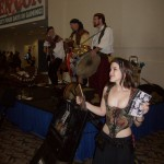 Water Street Bridge entertains people as they head into the Exhibition Hall at Gen Con 2010. A comely wench sells CDs.