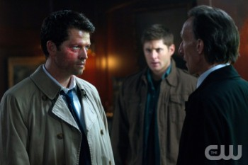 God-Castiel faces off against Death, with Dean Winchester looking on.