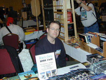 John O'Neill selling BLACK GATE magazine in the Windycon Dealer's Room.