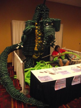 A dragon made of balloons. The light green balloons on the ground are for the wings in progress.
