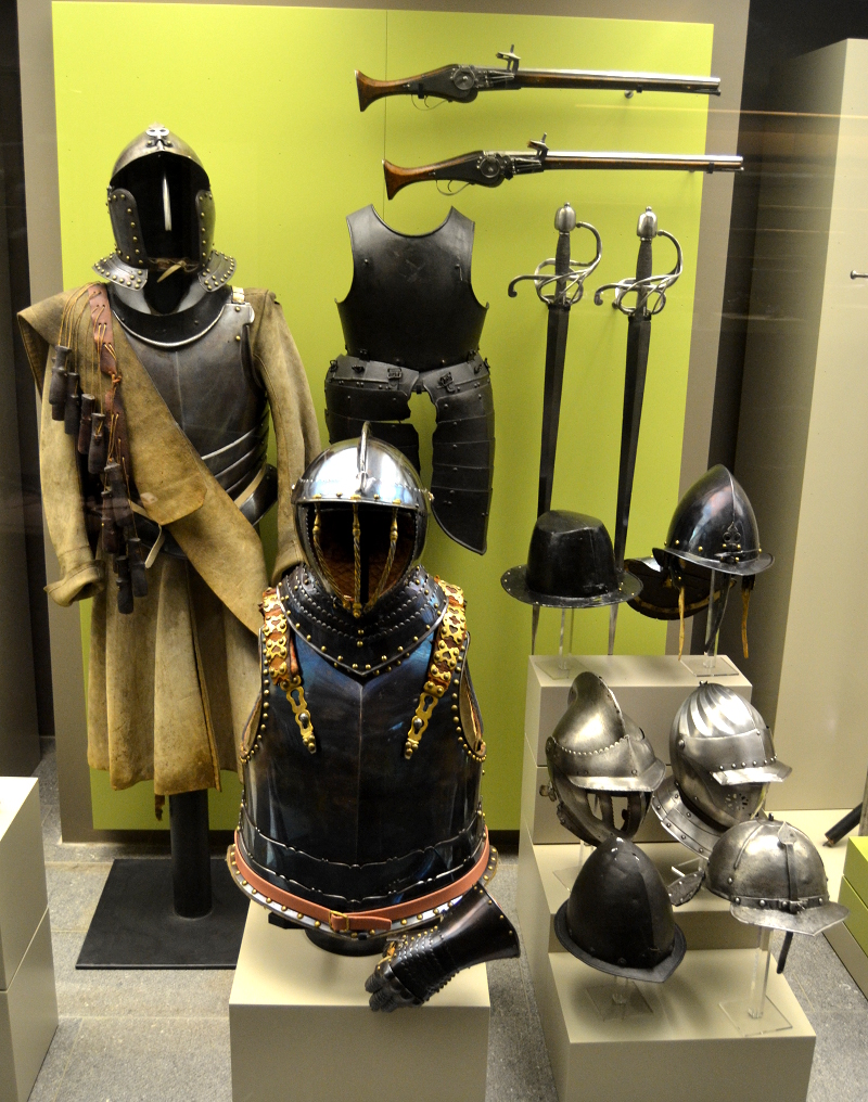 A collection of 17th century arms and armor. The blued steel breastplate in the front dates to the Thirty Years War (1618-1648). Bluing is done by heating the metal to 300°C, polishing it, and reheating it to the same temperature. While it looks nice, it's not very practical because rust can form under the blue exterior layer.