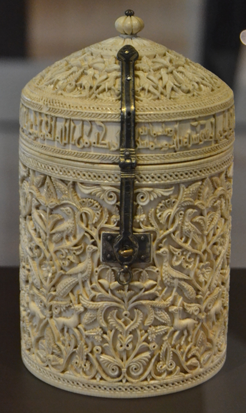 The Zamora pyxis, an ivory box with a dome-shaped lid that opens and closes with a hinge and a silver clasp with niello detailing. The delicate carving includes arabesques, palmettes, gazelles, peacocks, and other birds that recreate a palace garden. An Arabic inscription in Kufic-style calligraphy on the base of the lid indicates the date of manufacture (353 after Hijra / 964 AD), the artist (Durri al-Salir), the person who commissioned it (Caliph Al-Hakam II) and the recipient (the caliph's favorite, Subh).