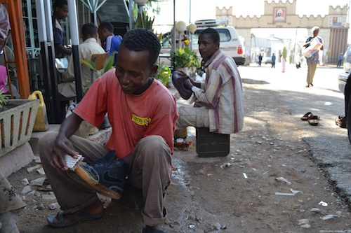 These shoe shiners in Harar, Ethiopia, use munitions boxes to store their tools and also as seats.