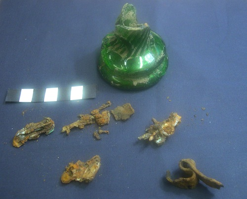 A fragmentary witch bottle with corroded metal remains that appear to be bent pins. Photo courtesy Portable Antiquities Scheme.