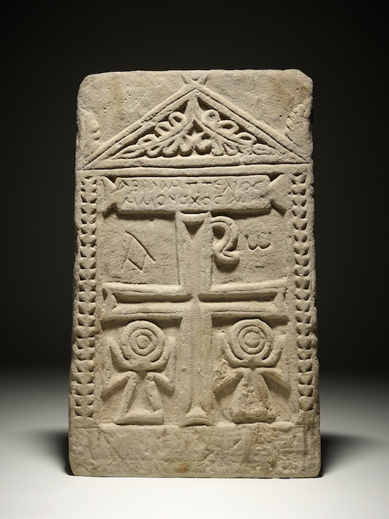 """Gravestone of 'Abraham, the perfected monk', Egypt, 7th century AD. Many early Coptic Christian carvings show the anceitn Egyptian sign for """"life"""", the ankha, next to Christian symbols such as the cross and the Chi-Rho. © The Trustees of the British Museum"""