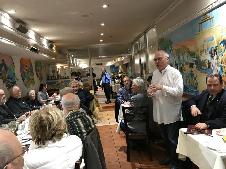 Leslie Klinger giving speech at Sherlockian dinner at Bouchercon 2017 in Toronto. Laurie R. King is seated behind him to his left.